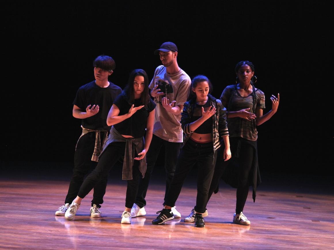 group of 5 students on stage performing dance