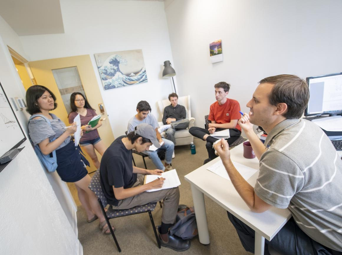 six students meet with a professor in his office.