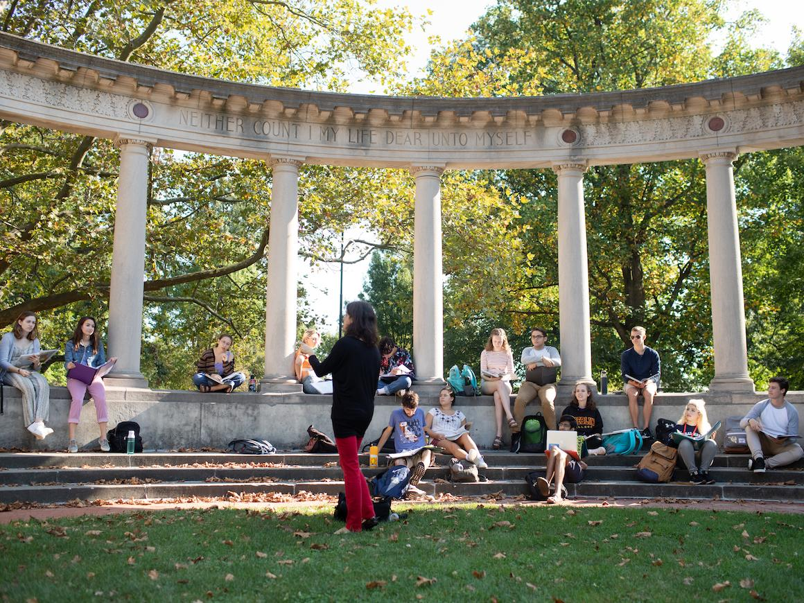 groups of students listen to a professor give a lesson while sitting outdoors under an arch.