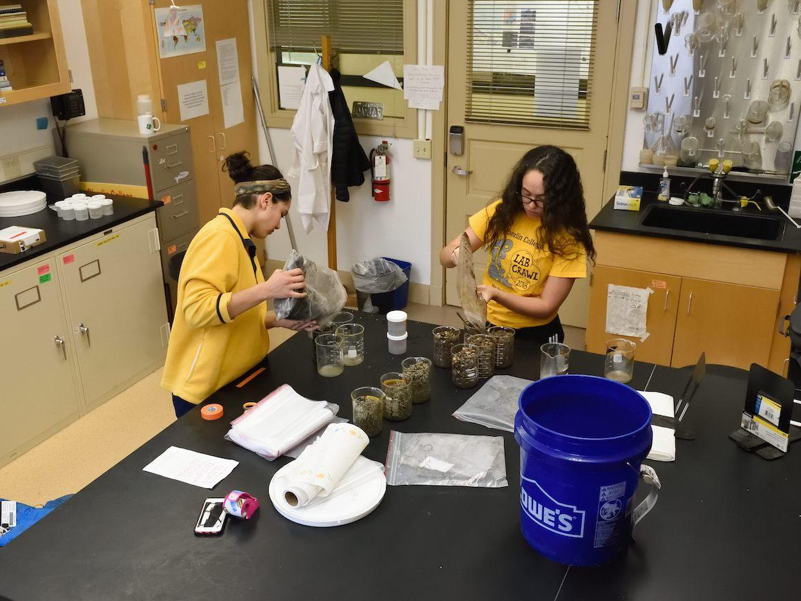 two students in a lab pouring soil samples into plastic bags
