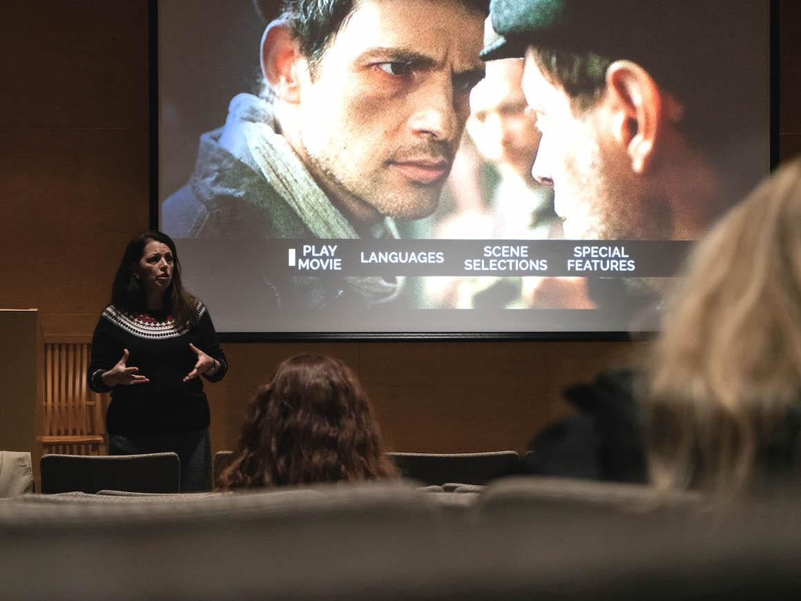 female professor in auditorium talking to audience while standing in front of a large movie screen.