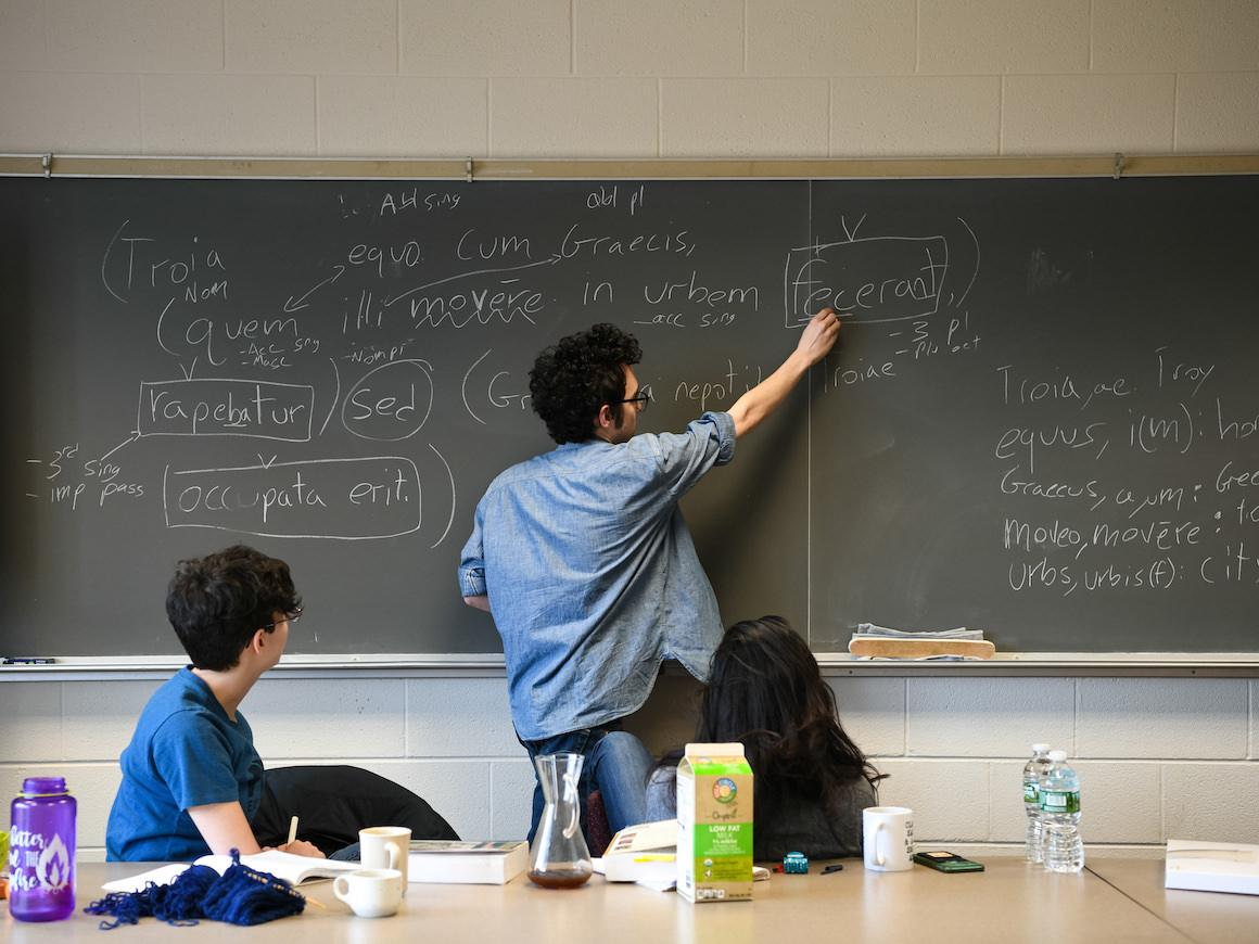 two students in classroom looking at Latin words being written on blackboard by another student.
