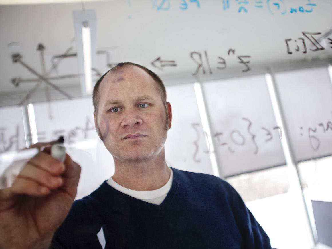 man using dry erase maker to write math formulas on a clear board,