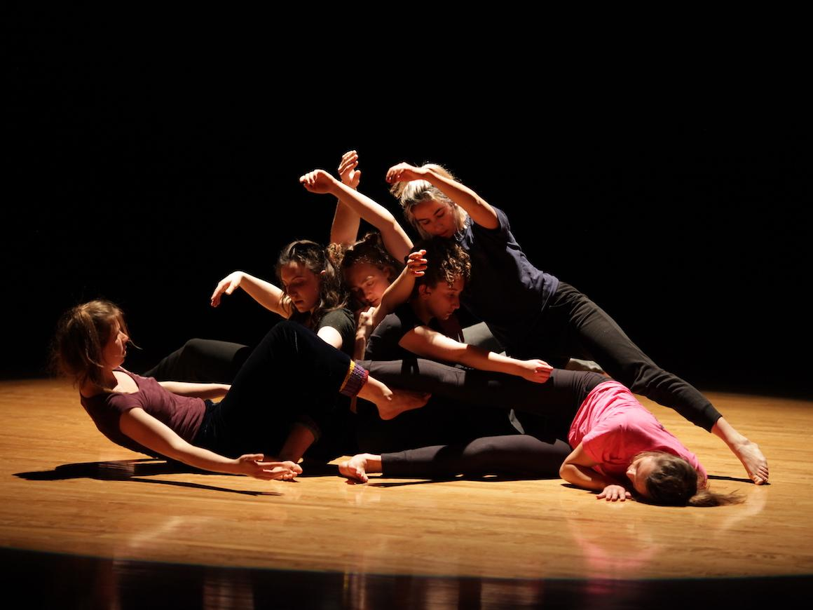 six student dancers piled on floor.
