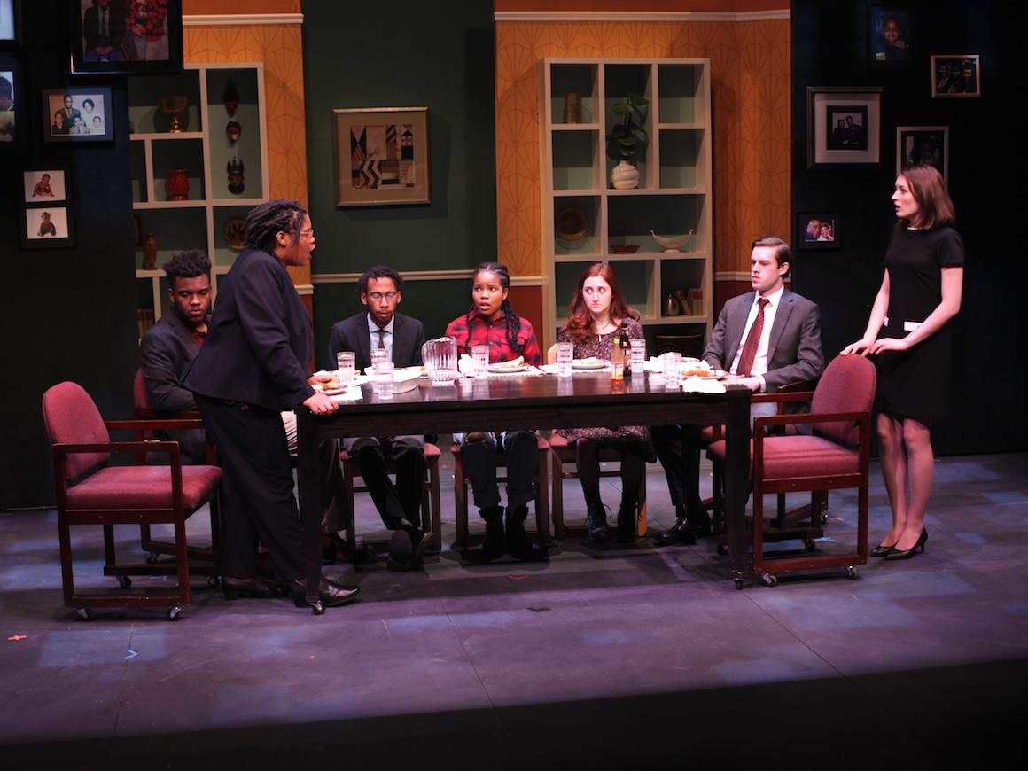 a play featuring a black family and white family seated around a table