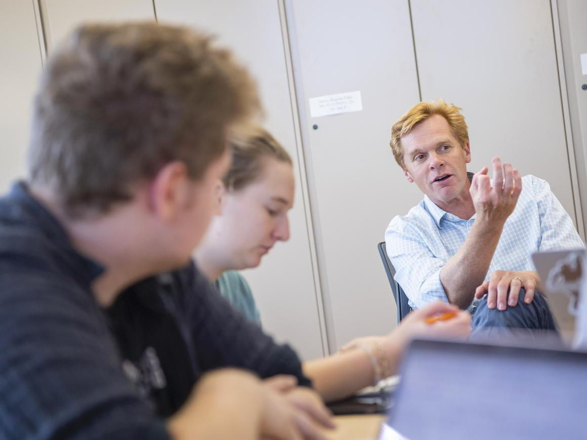 male professor discussing a course with two of his students.