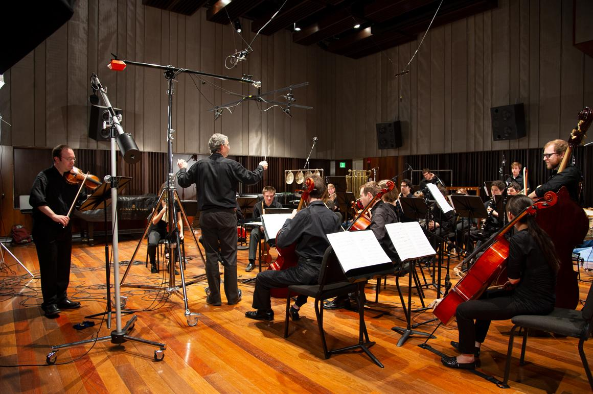 A string and wind ensemble in the recording studio with microphones all around.