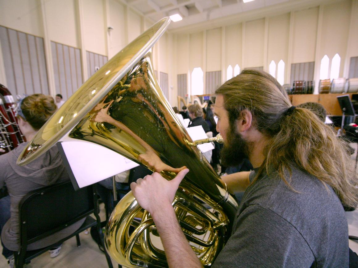 conservatory tuba student rehearses in one of large practice rooms.