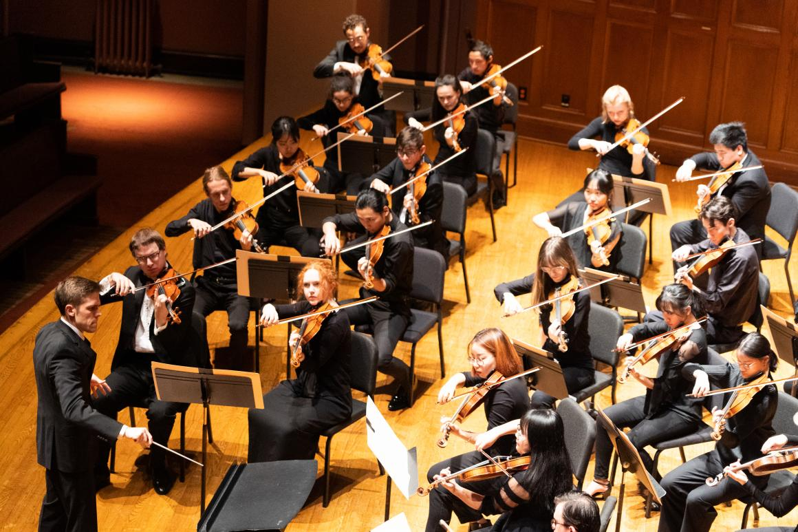 conductor leads an orchestral string section