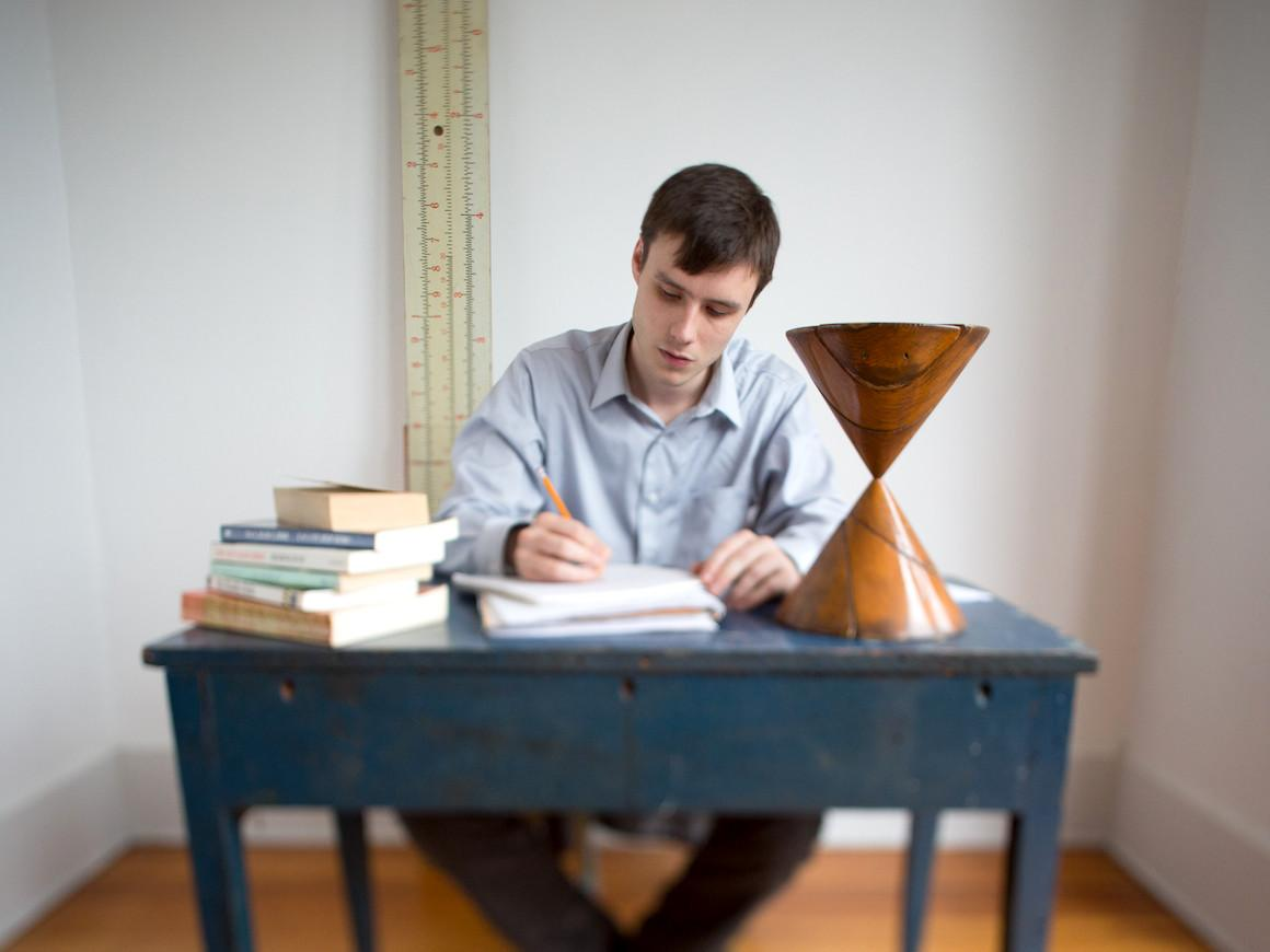 student sitting at desk writing with a stack of books at his side