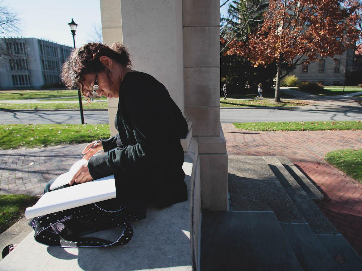 female student sitting on steps reading a book