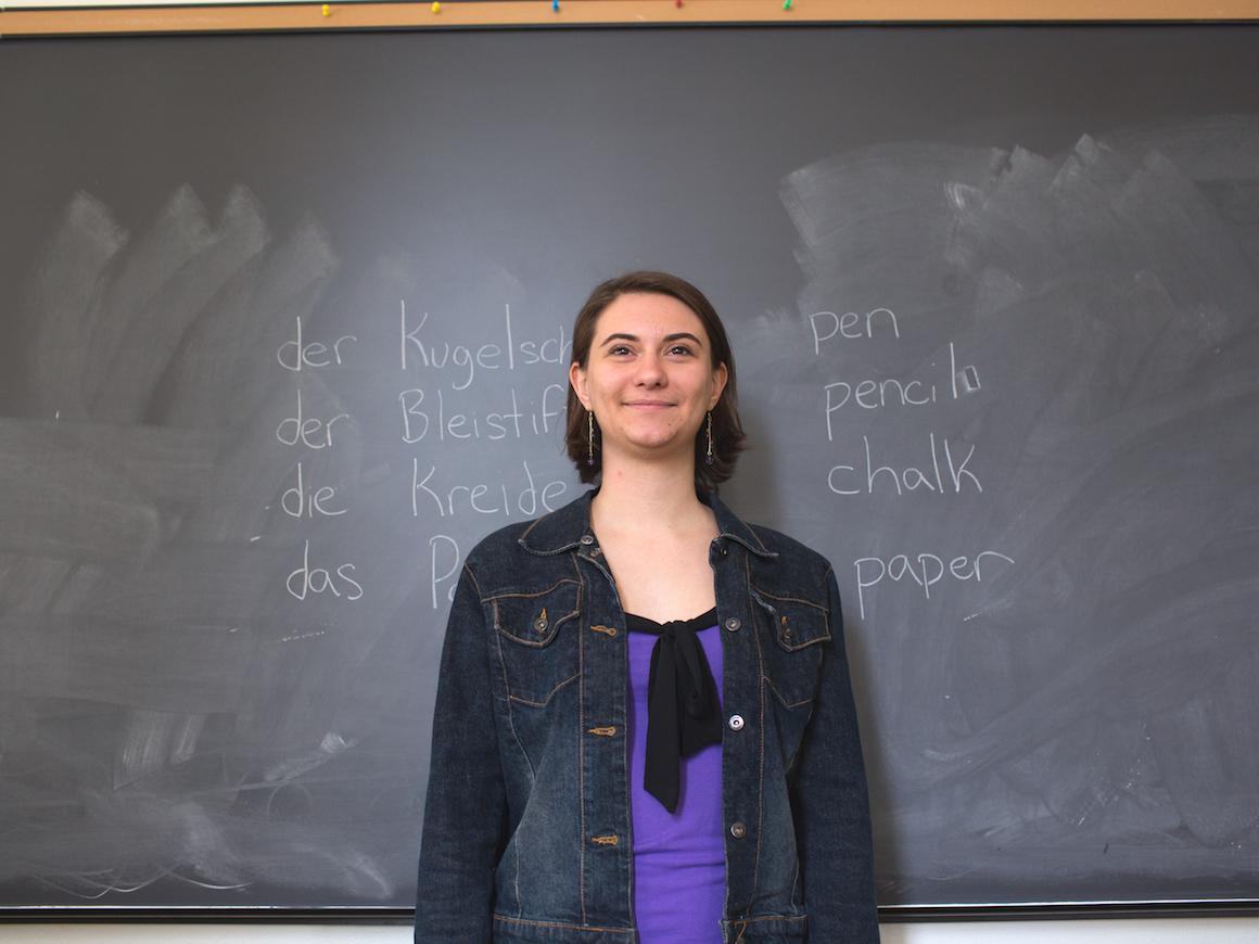 student standing in front of a blackboard with list of German words