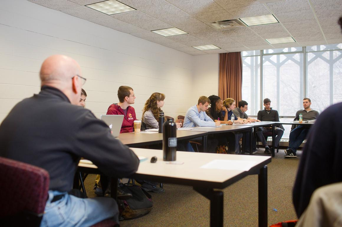 A professor and about 10 students are seated around a table in a sunny classroom.