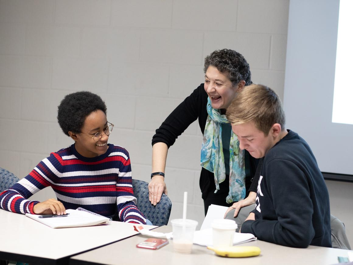 woman history professor shares a laugh with two students.