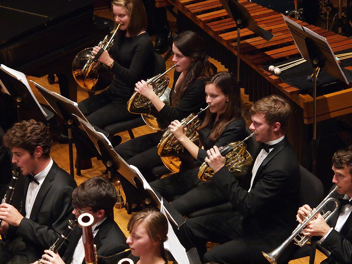 Close-up of 4 French horn players performing in an orchestra