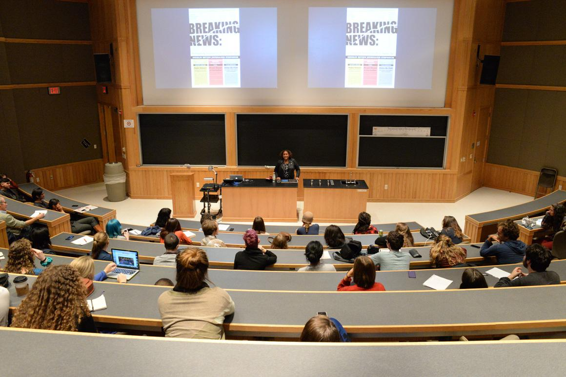 A woman speaks to a lecture hall audience. The screen behind her has a slide with the words 'Breaking News.'