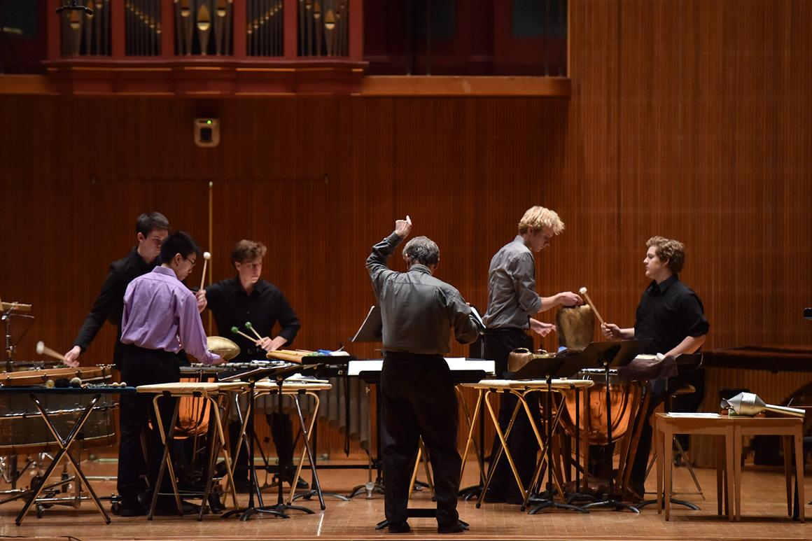 Five percussionists and conductor performing on stage