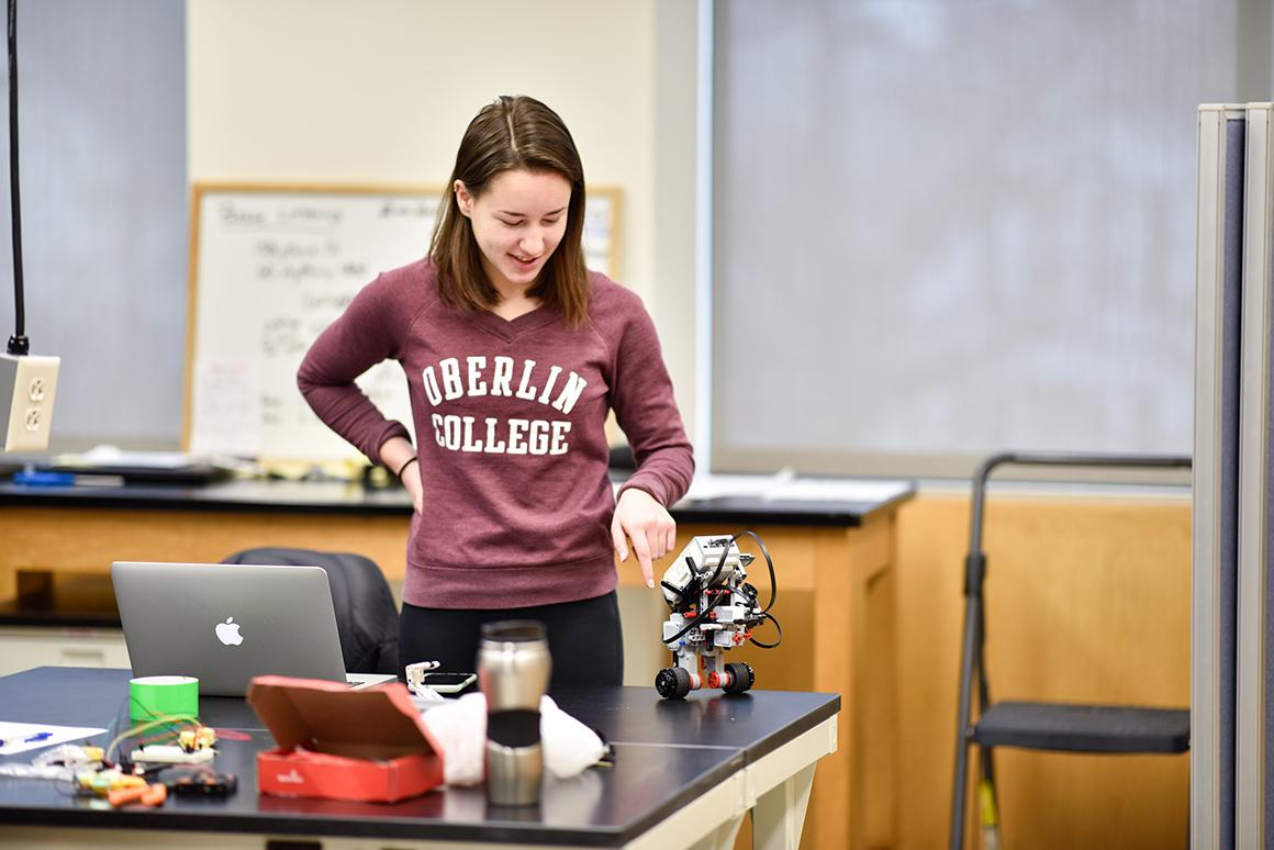A student looks at a LEGO robot on a lab table