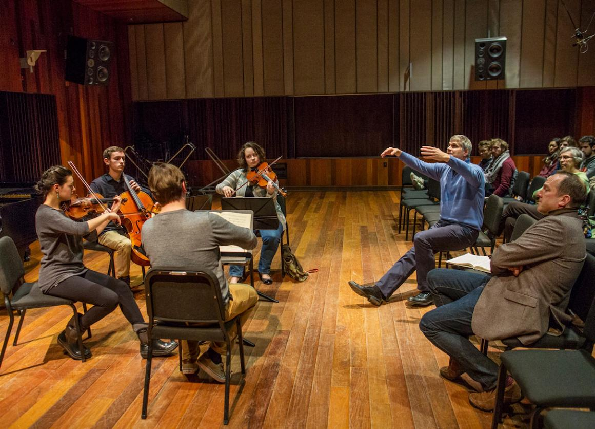String players seated in a circle receiving instruction