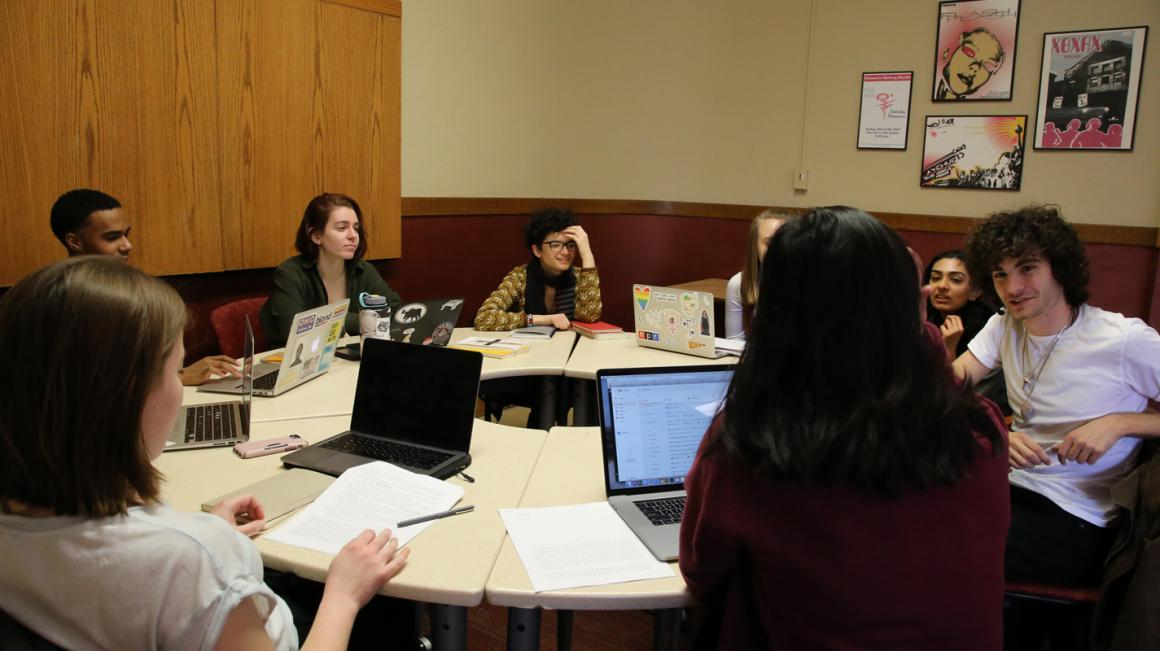 A group meets around a round table, laptops open and papers out.
