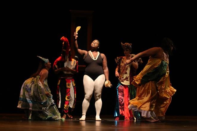 Dancers on stage. A woman gazes into a handheld mirror, surrounded by others in colorful costumes.