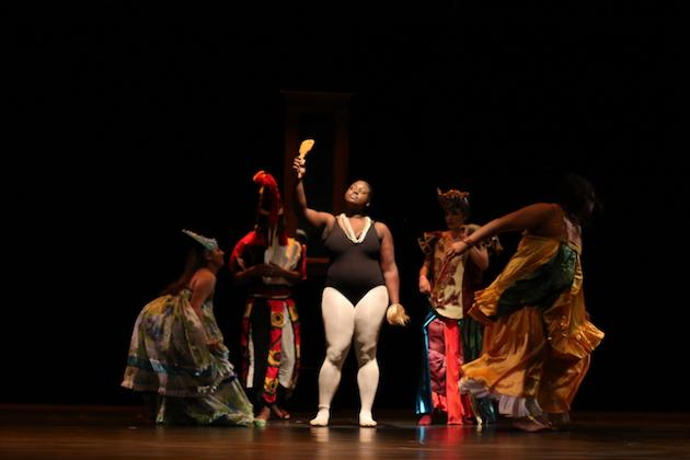 Students performing on stage. The student in the center has a black leotard and white tights on.