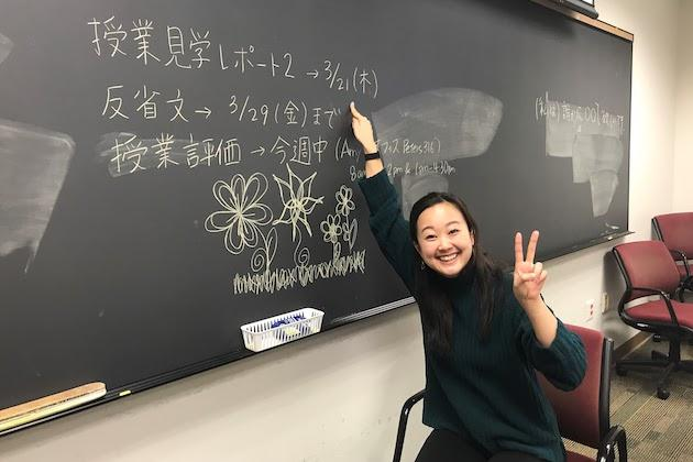 A lecturer of Japanese smiling in front of a blackboard.