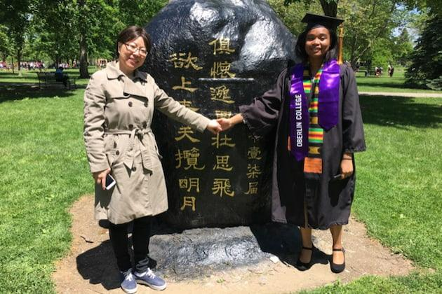 Fang Liu and a student in front of the rock on Tappan Square.