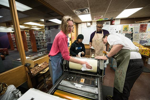 With library stacks in the background, 4 people wearing aprons set up a letterpress machine.
