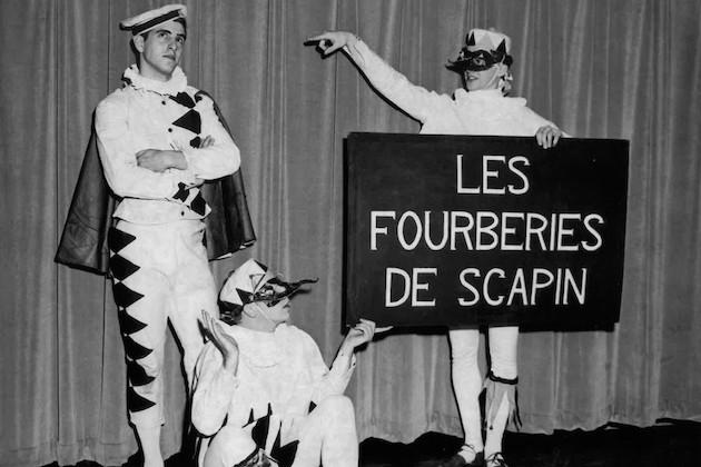 """Three people on stage, one of them holding a sign that reads, """"Les fourberies de scapin."""" Black and white."""