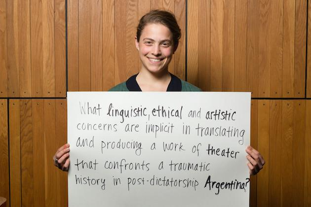"""A student holding a sign that reads, """"What linguistic, ethical, and artistic concerns are implicit in translating and producing a work of theater that confronts a traumatic history in post-dictatorship Argentina?"""