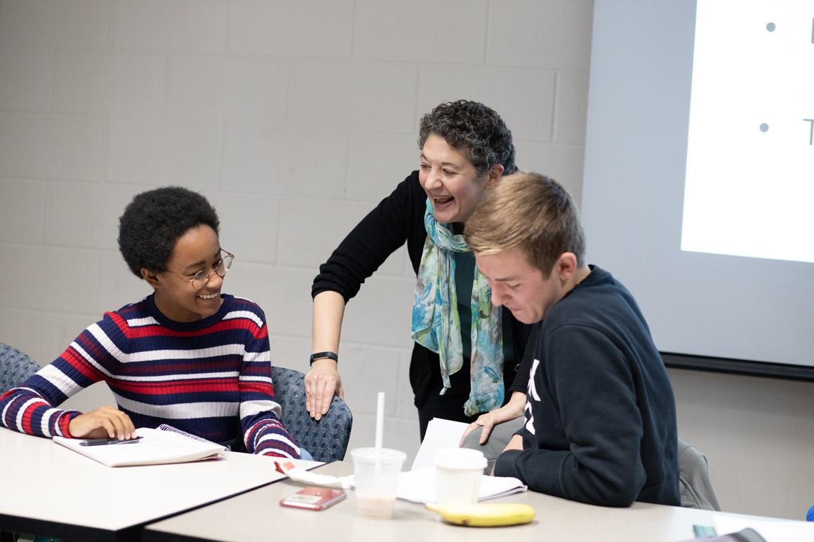 A professor shares a laugh with students during class.