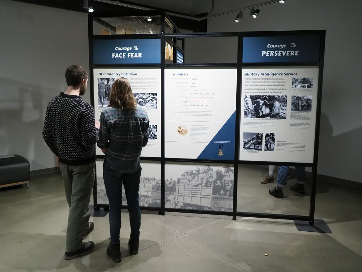 People view a poster at an exhibit.