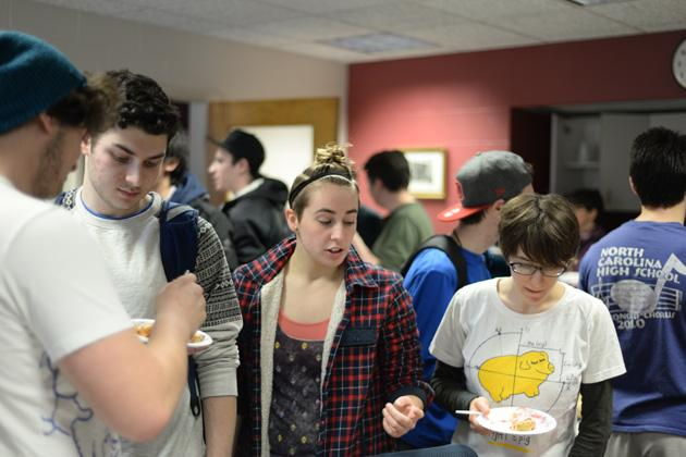Students mingle and eat pie.