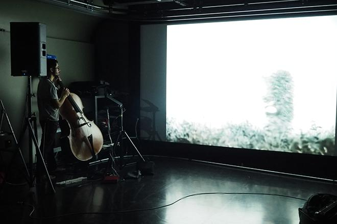 A bassist performs alongside a projection screen.