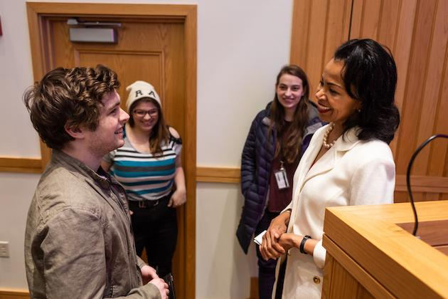 Gina Abercrombie-Winstanley in a white suit chatting with students.