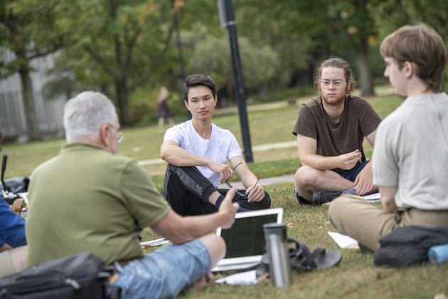 Professor Marc Blecher and students sitting on the grass.