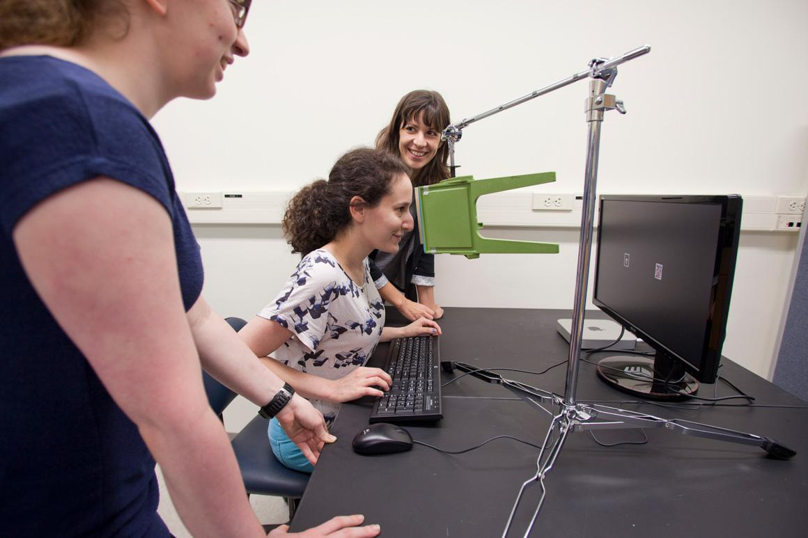 Students test a subject using visual stimuli on a computer screen.