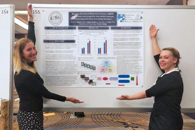 Two students show their research poster, which includes bar charts, a Venn diagram, and sections of text titled Introduction, Method, Results, and Summary.