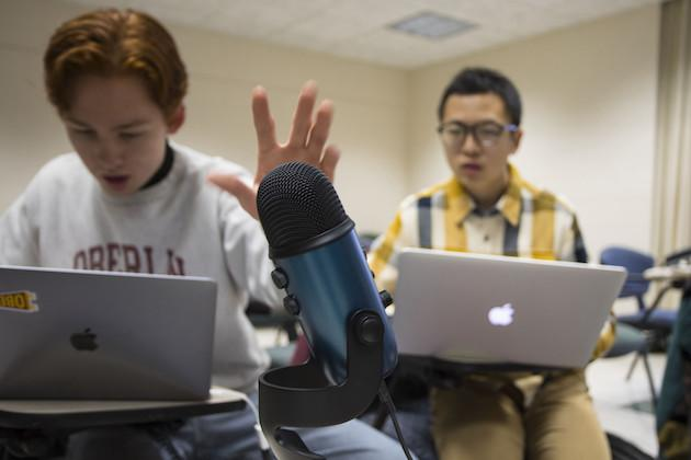 Two students recording a podcast in a classroom.