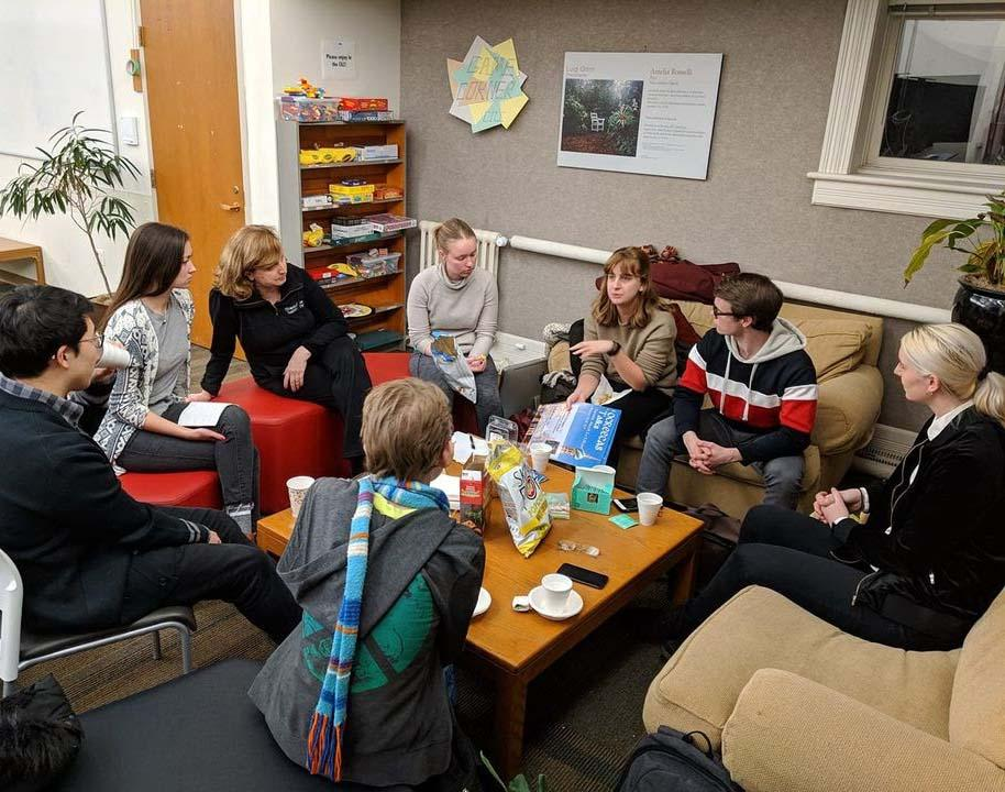 A group of 8 people meets in a lounge.
