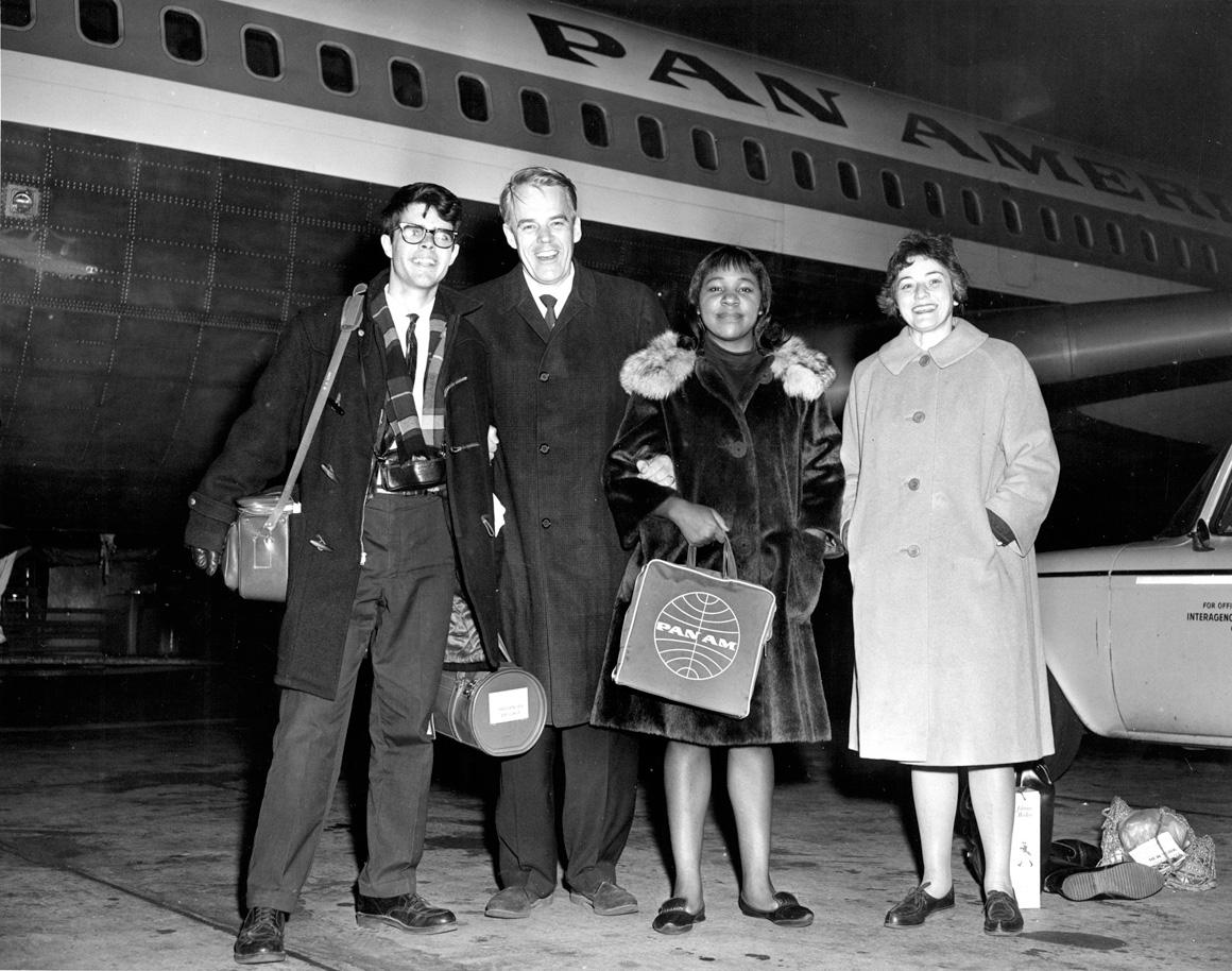 Four travelers stand beside a Pan American Airlines plane.