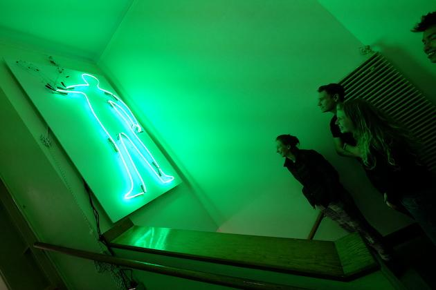 Students looking up at a green neon sign shaped like a human.
