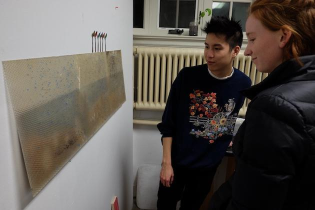Two students looking at artwork.