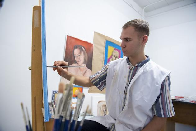Steven Mentzer painting in a studio.