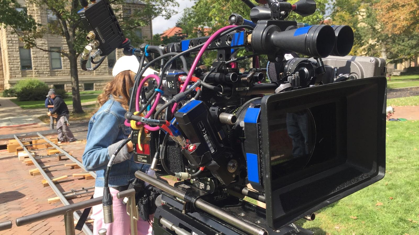 A student looking through a professional video camera on Tappan Square.