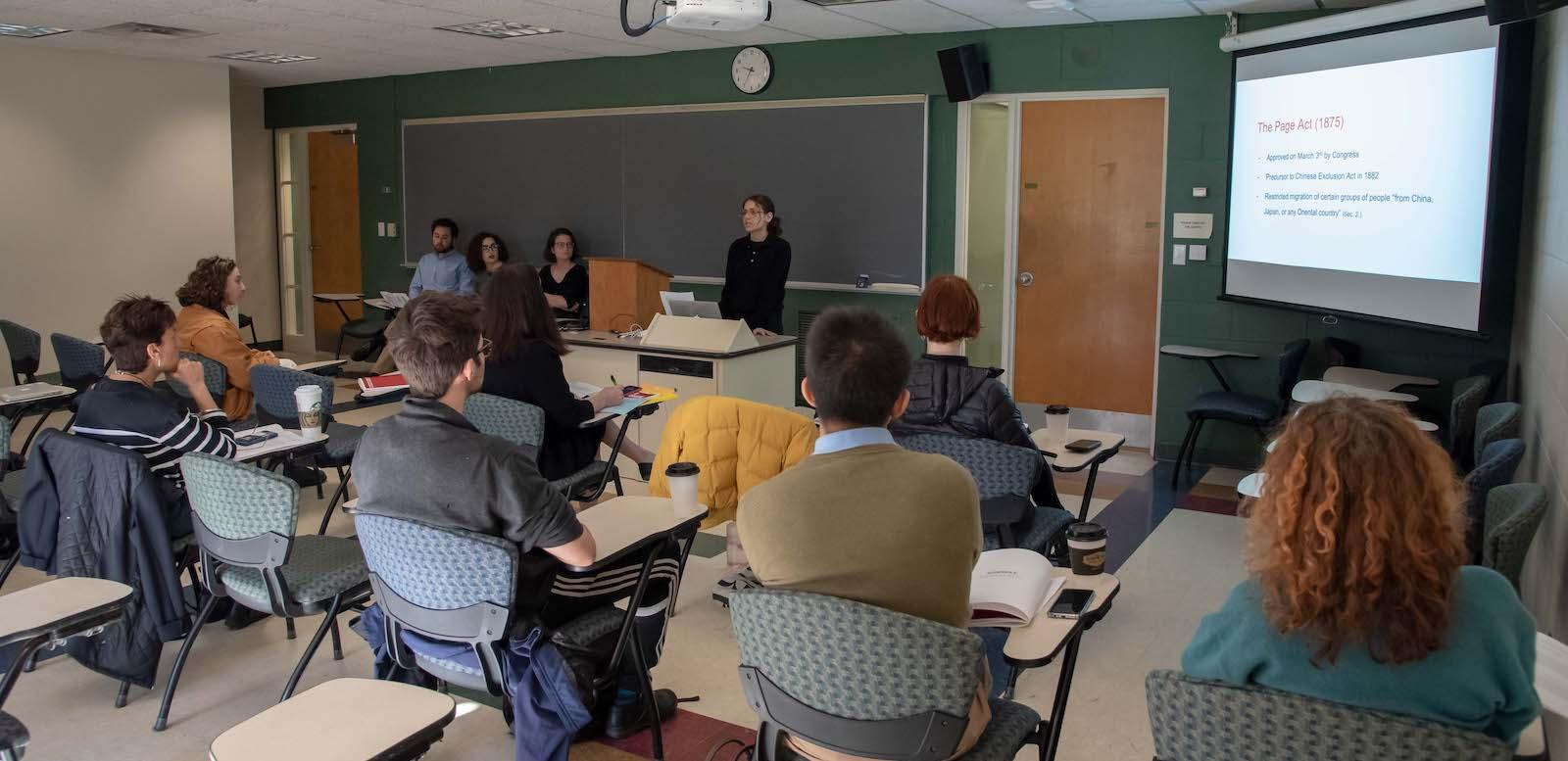 classroom of students with three in the front making a presentation