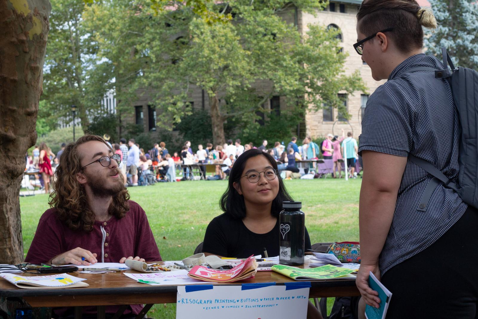 students communicate at an information table