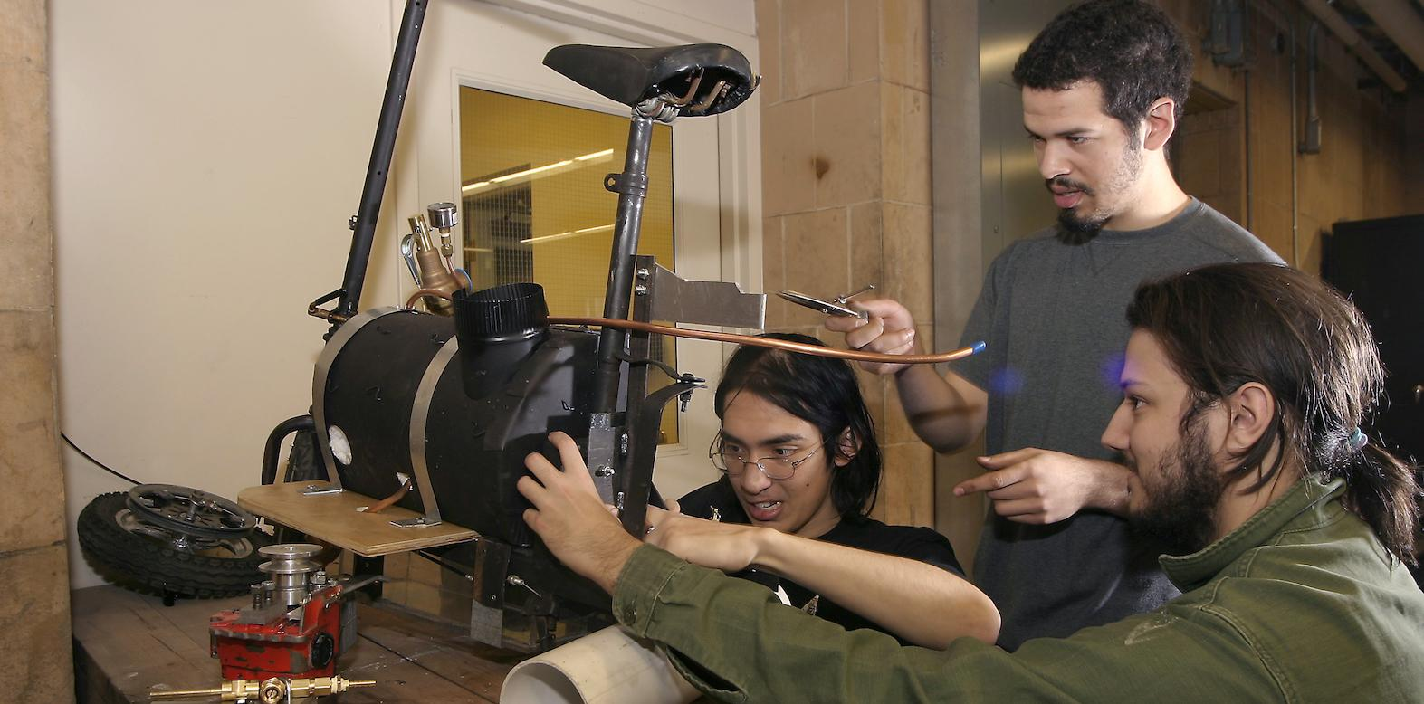 Three students at a workbench make adjustments to a device that includes a bicycle seat and an enclosed vessel