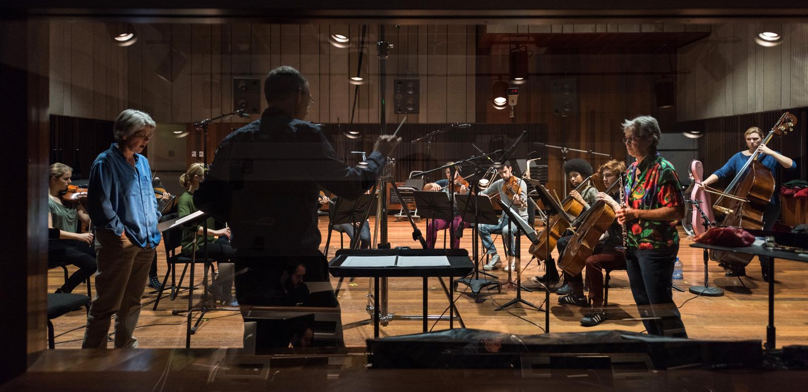 A string ensemble and oboist in the recording studio, as seen through the control room glass.